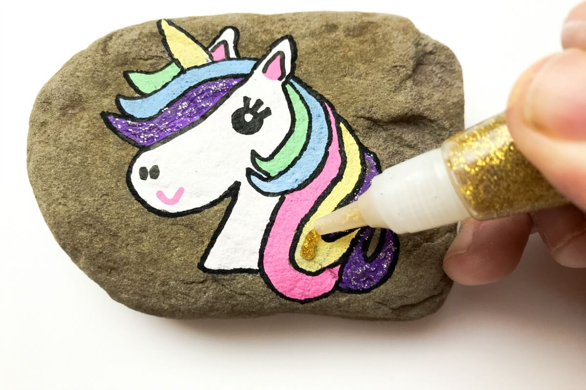Add glitter to unicorn rock painting idea