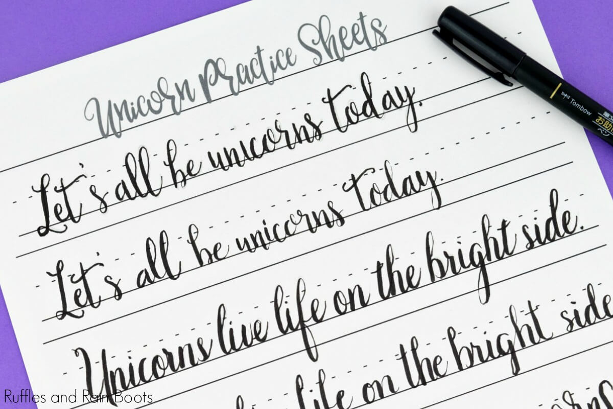 unicorn hand lettering sheet in black ink on purple calligraphy clipboard