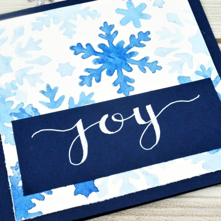 close up of watercolor snowflakes in three shades of blue with hand painted text reading joy