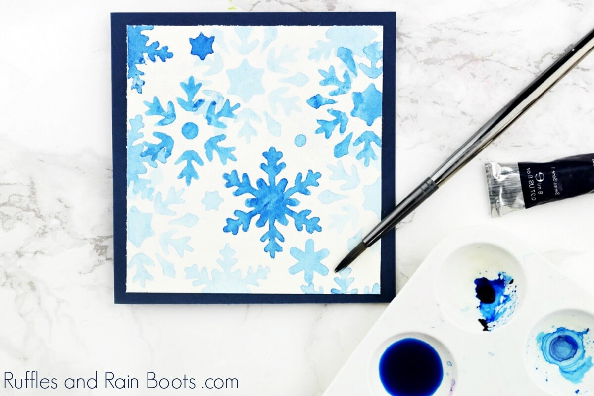 snowflake stencil template card with watercolor brush and blue watercolor paint