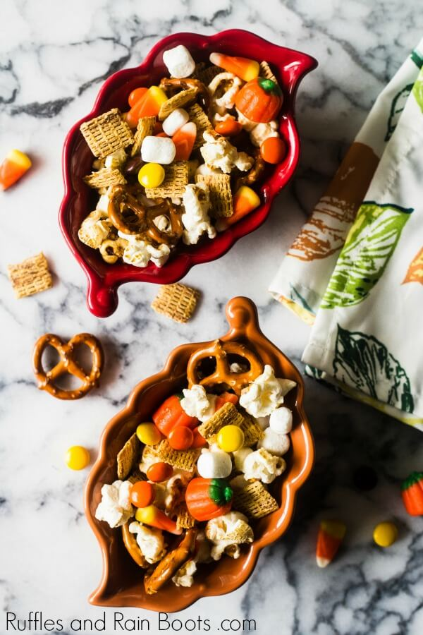 two leaf bowls full of fall autumn snack mix on a marble table with a kitchen towel