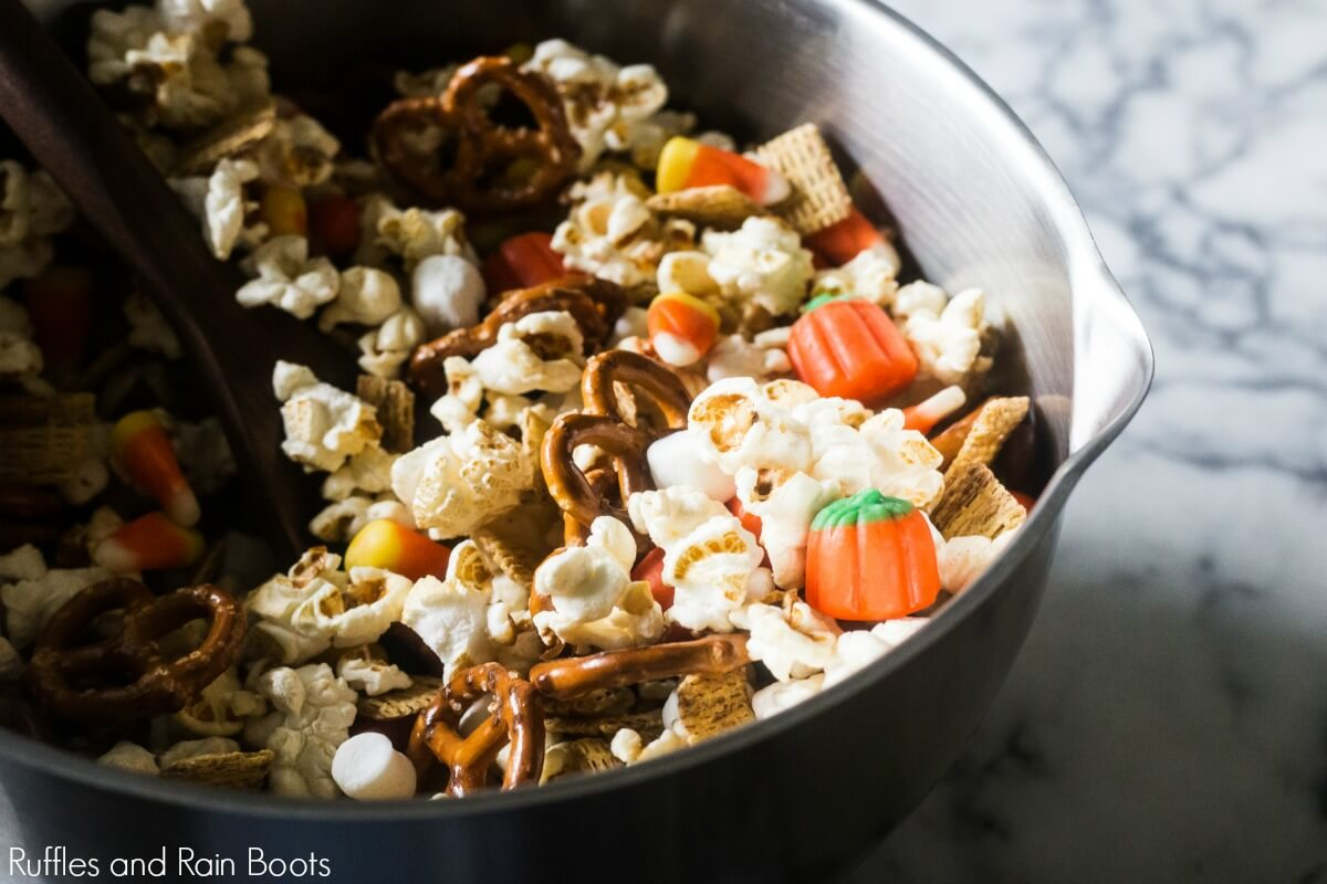 large bowl and spoon mixing together a sweet and salty popcorn fall snack mix
