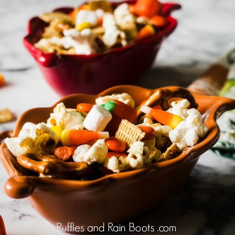 fall snack mix with popcorn pretzels marshmallows and candy in a brown leaf bowl on a marble table
