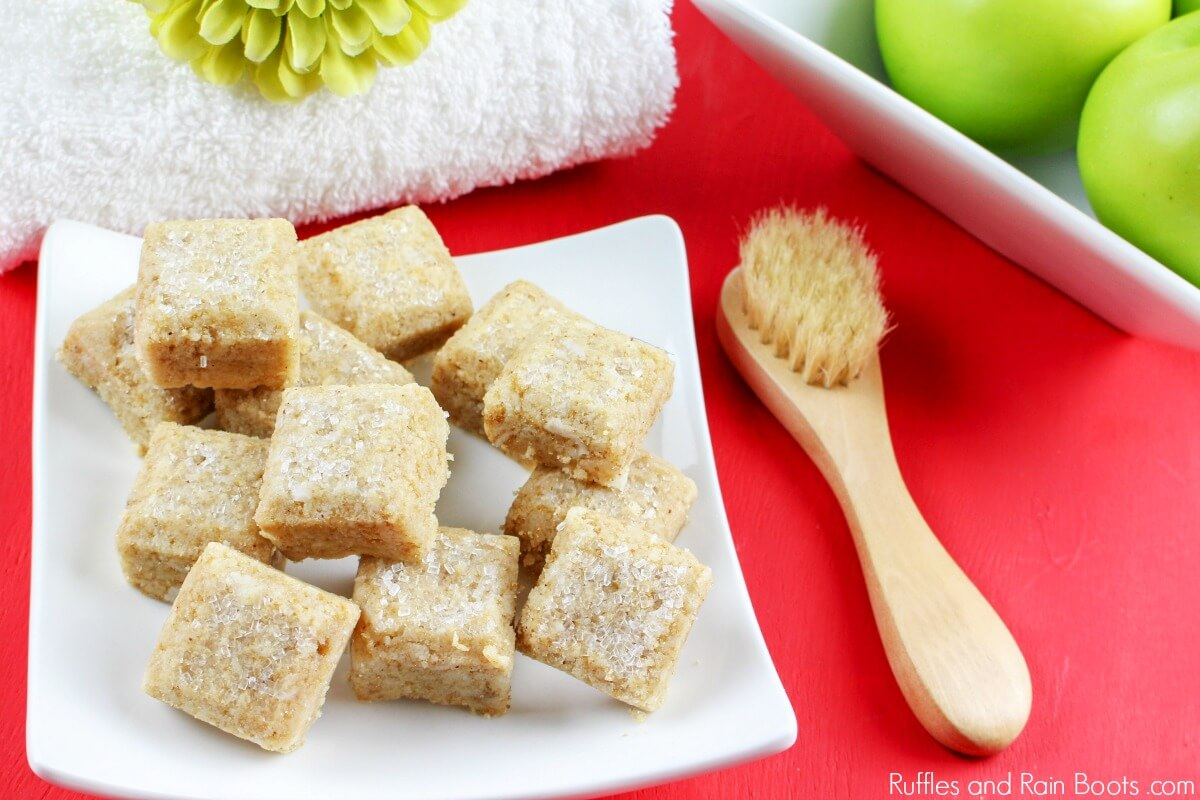 stack of apple pie sugar scrub cubes on red background with bath supplies