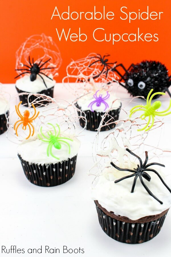 cupcakes with white frosting, sugar spider webs, and plastic spiders on a white and orange background with text which reads Adorable Spider Web Cupcakes