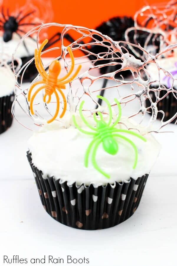 close up of a spider cupcake with a spun sugar web and plastic spiders on frosted cupcakes with text which reads Ruffles and Rain Boots