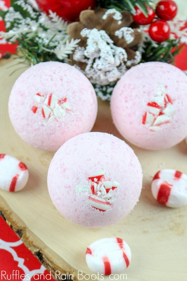 Candy Cane Christmas bath bomb recipe with 3 bath bombs on a wood slat with candies