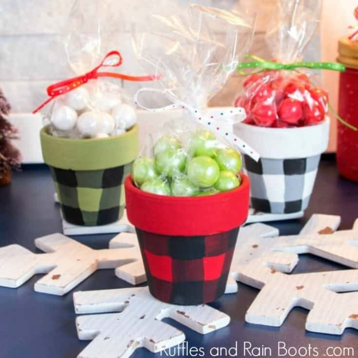 Three Christmas clay pot jars painted in Buffalo plaid on holiday background