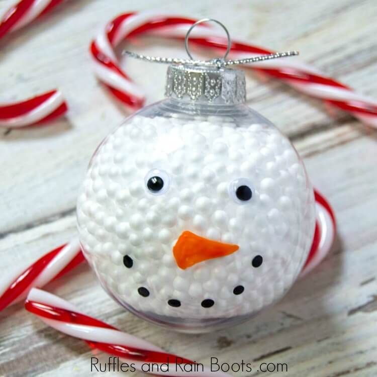 close up of filled snowman ornament DIY craft on wooden background with candy cane