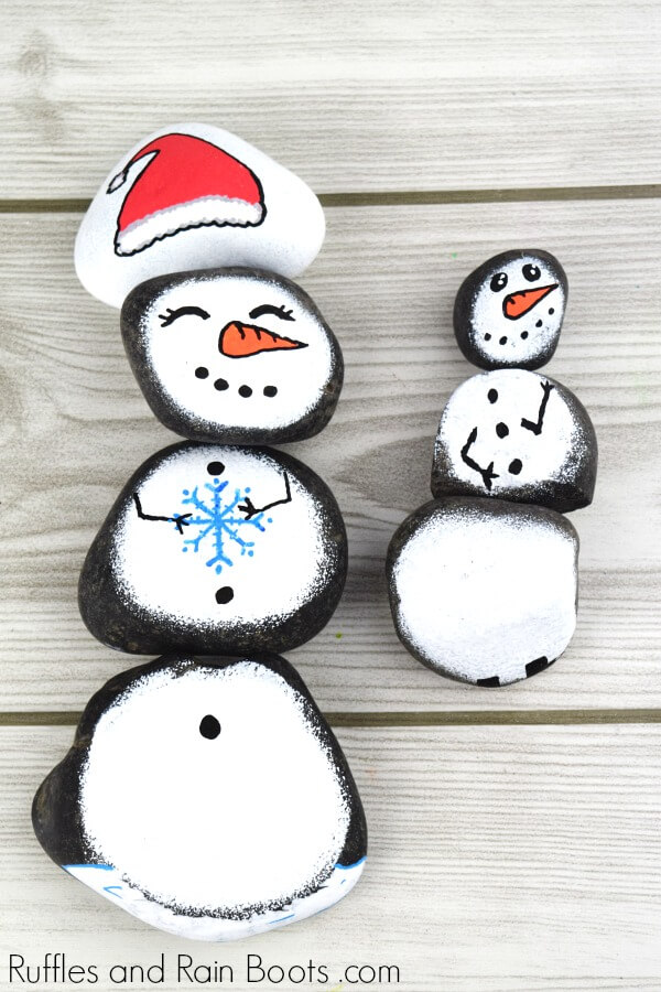 Snowman story stones on white wood background