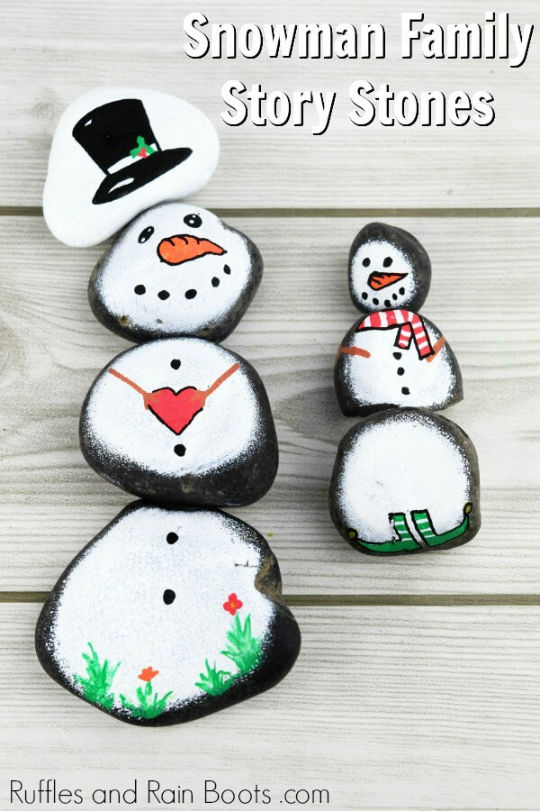 Montessori story stones snowman rock painting on white wood background with text which reads snowman family story stones