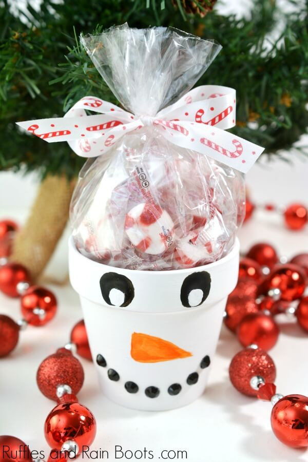 snowman painted terra cotta pot Christmas craft on holiday background