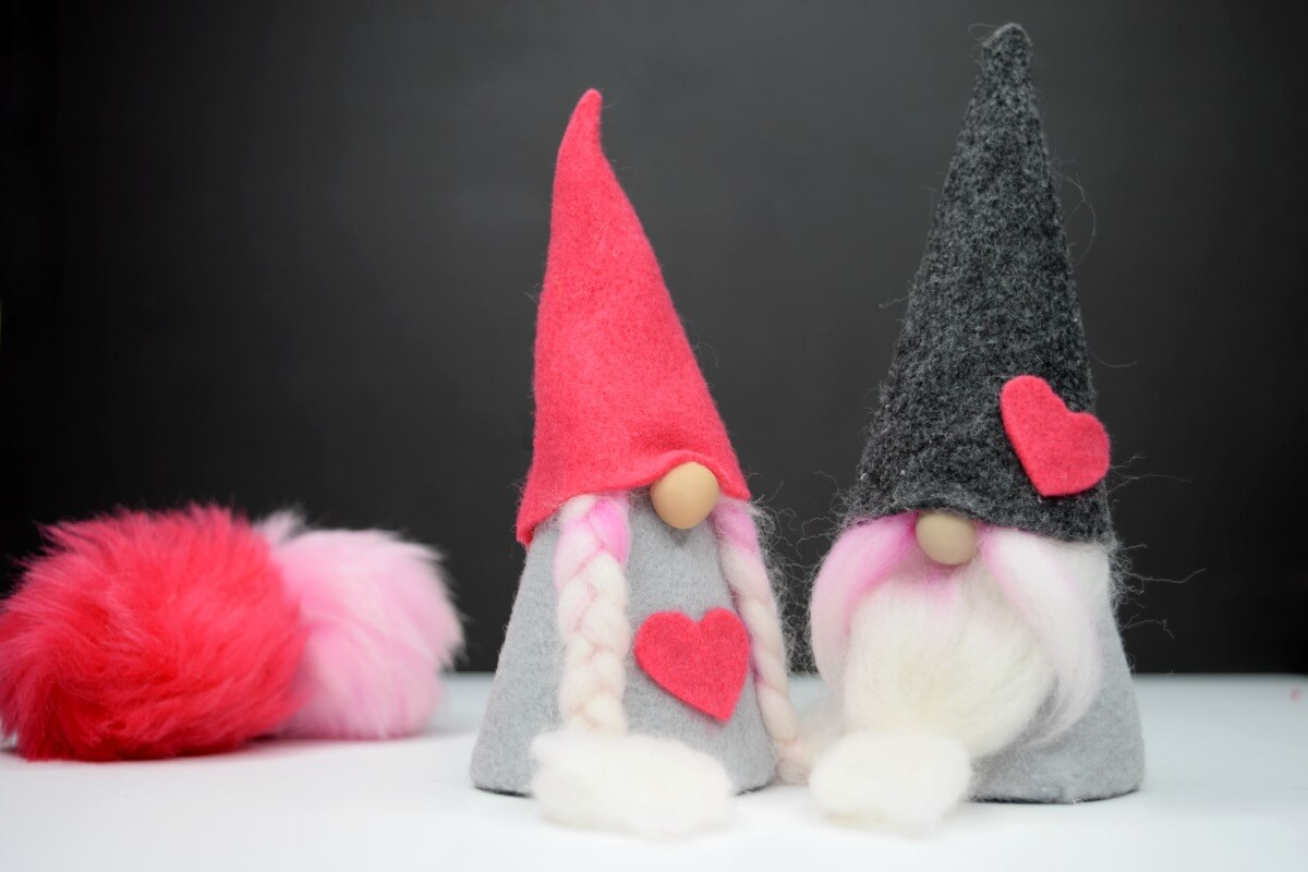 Valentine felt gnomes on black background with pink and gray gnome hat patterns