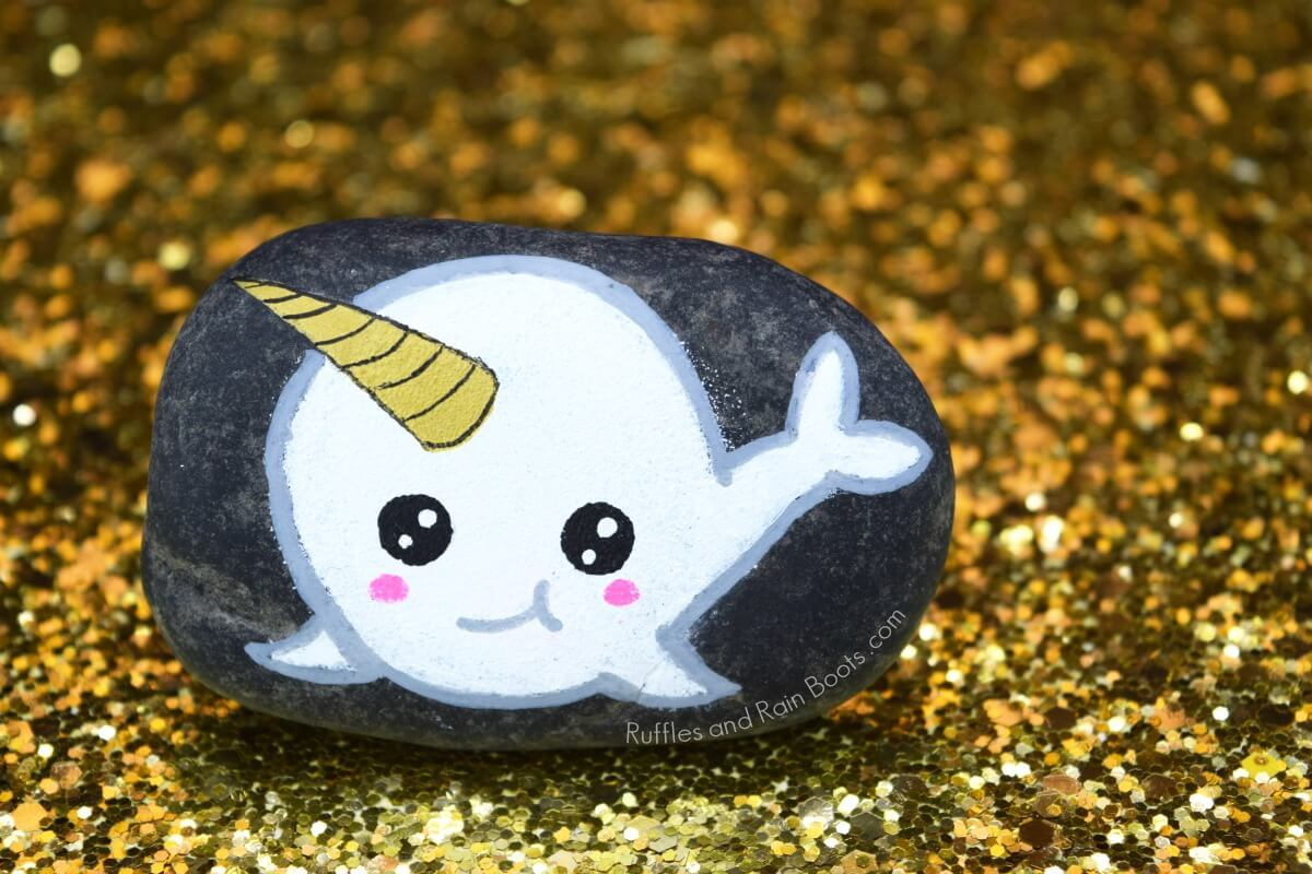 narwhal rock painting on gold glitter background
