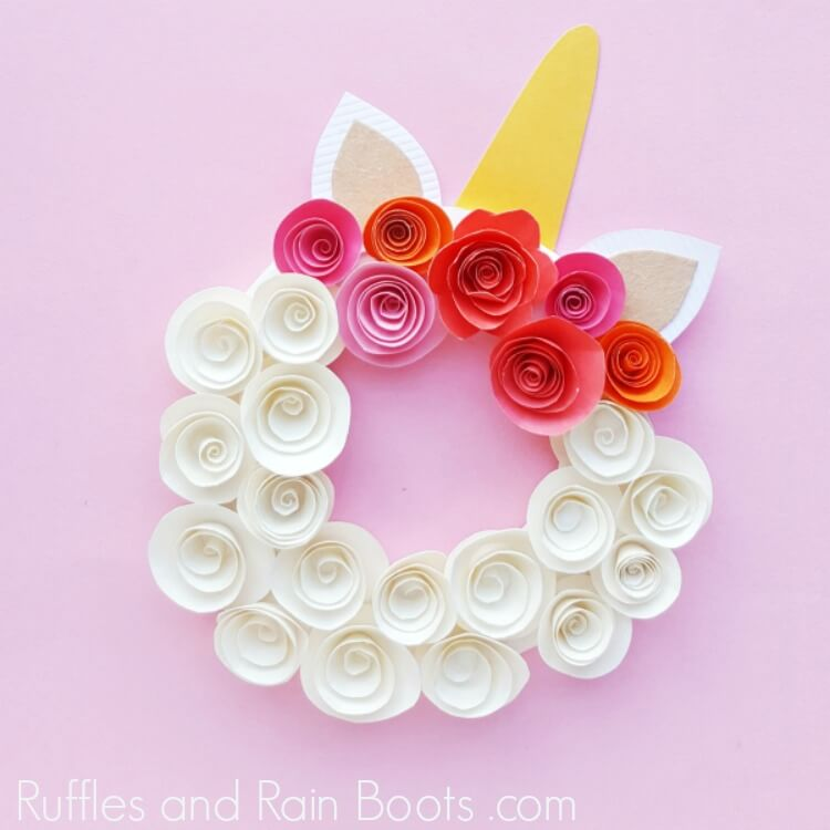 paper unicorn wreath on pink background with rolled flowers