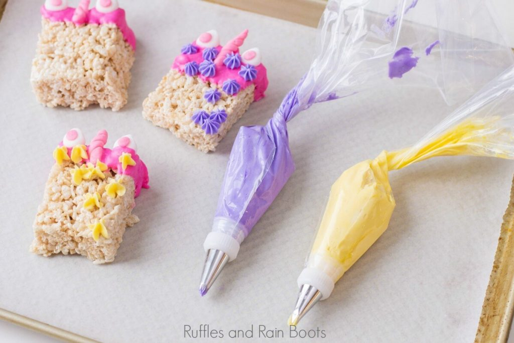 icing bags with pink and yellow colors showing how to add flowers to the unicorn rice krispies