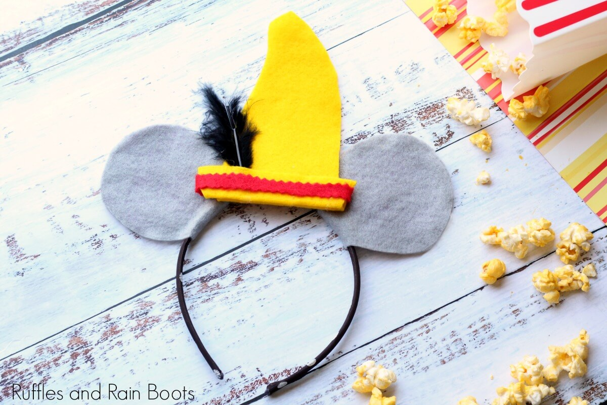 gray felt DIY Dumbo Mickey Mouse ears with hat on wood background with popcorn scatter