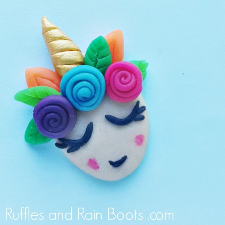 Unicorn polymer clay charm on blue background