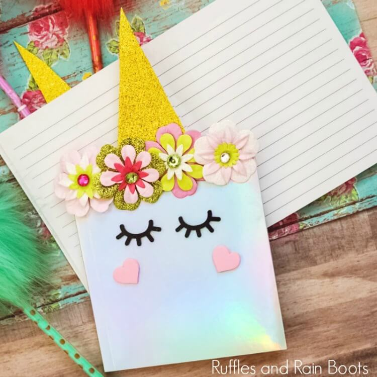 close of up DIY unicorn notebook laying on notepad with wooden background