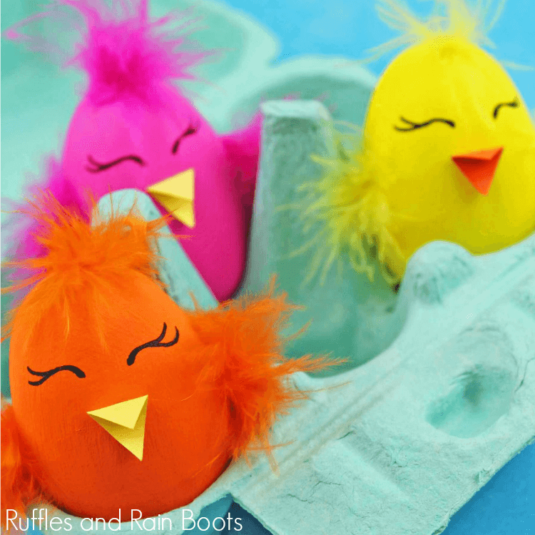 3 baby chick Easter eggs decorated and placed in a light blue egg carton