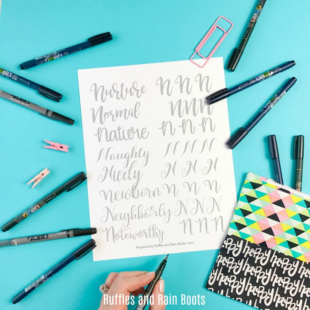 square image of letter n hand lettering practice sheet on blue background with colorful pens