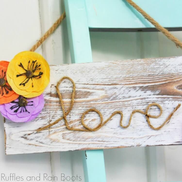 """blue chair with farmhouse sign for spring hanging from it which reads """"love"""" in rope"""