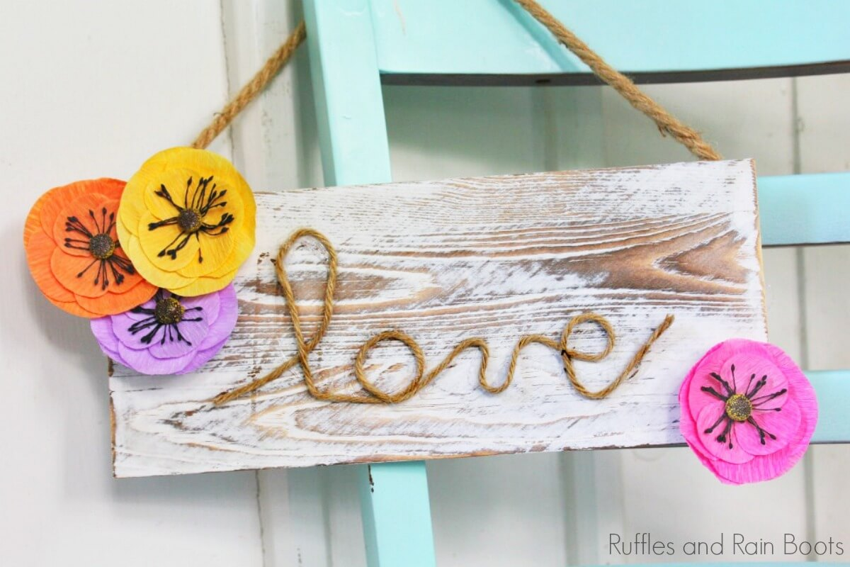"""farmhouse sign for spring which reads """"love"""" hanging on the back of a blue chair"""