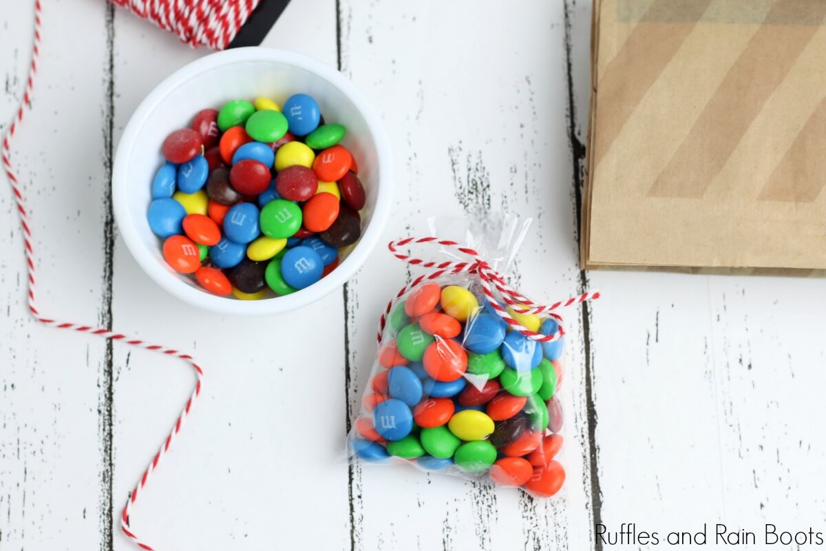 in process step of wrapping snacks of chocolate candies in a wrapper for the movie night in a jar on a white background