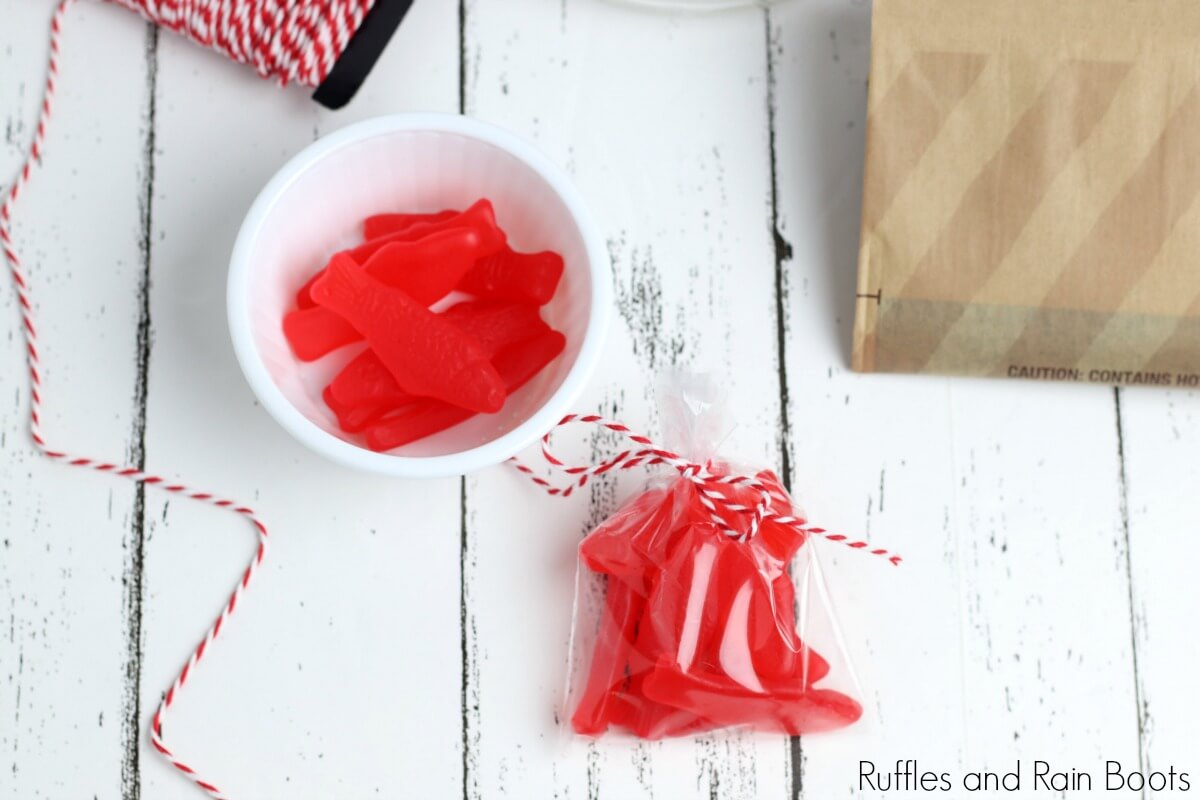 in process step of wrapping snacks of swedish fish in a wrapper for the movie night in a jar on a white background