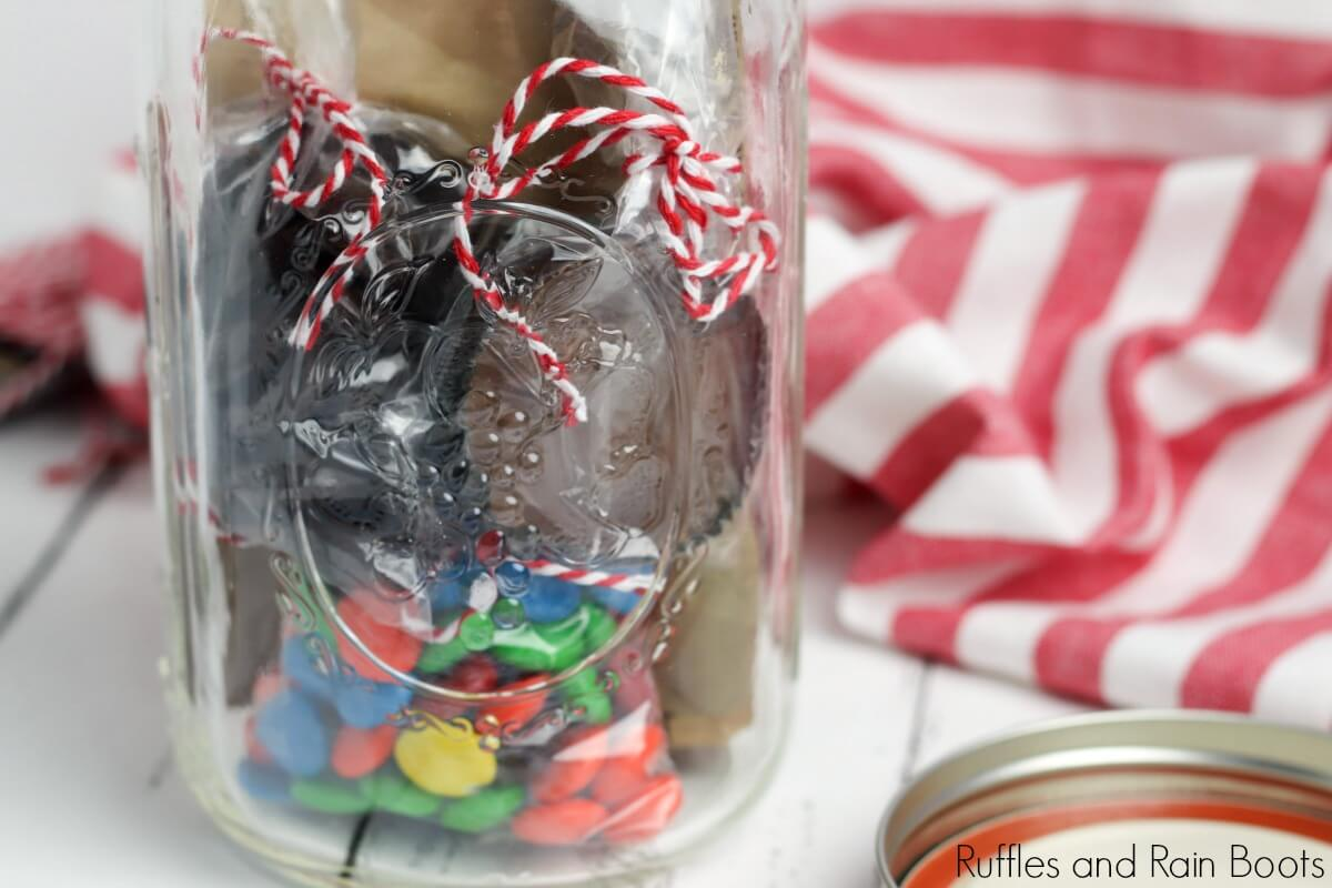 partially filled jar as in process step for the date night ideas for couples of a movie night in a jar on a white background