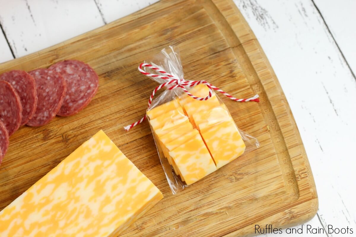 sliced cheese on a cutting board with sliced summer sausage and a portion of the cheese in a bag on a white background used to illustrate the materials to make a picnic date night in a jar craft
