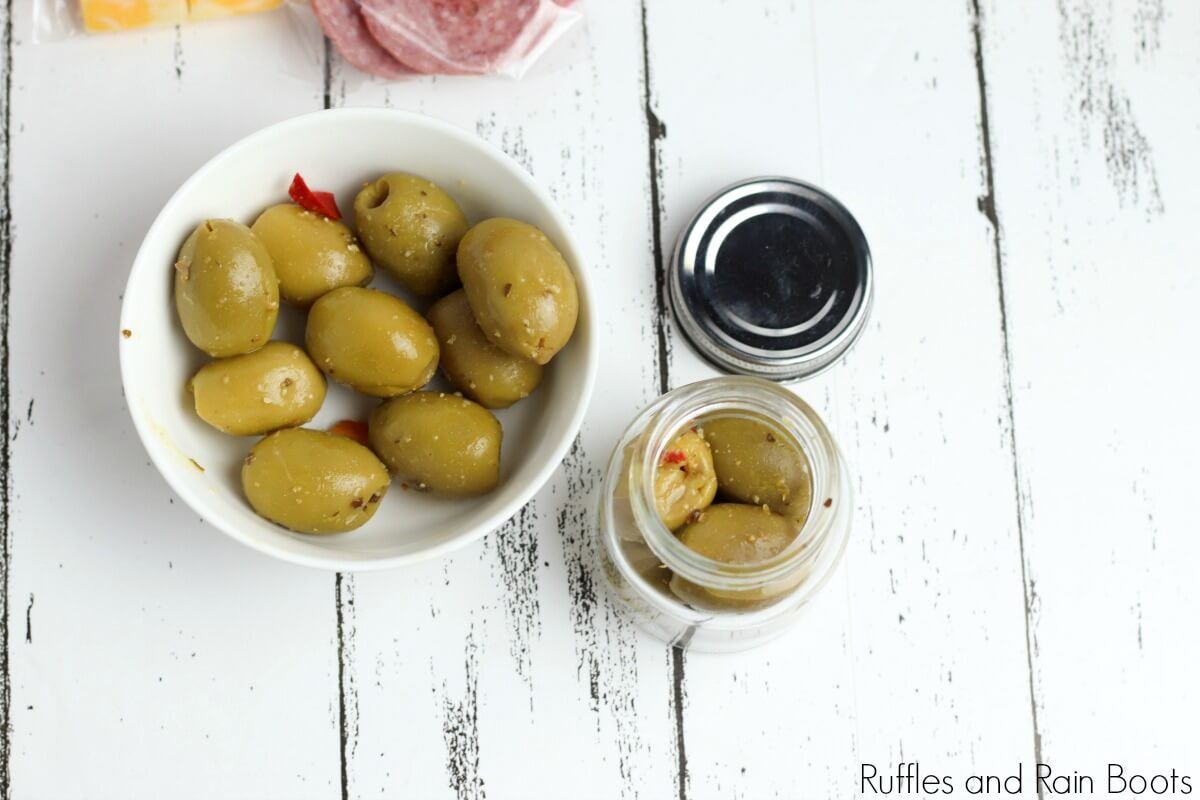 bowl of olives and smaller jar of olives on a white background used to illustrate the materials to make a picnic date night in a jar craft