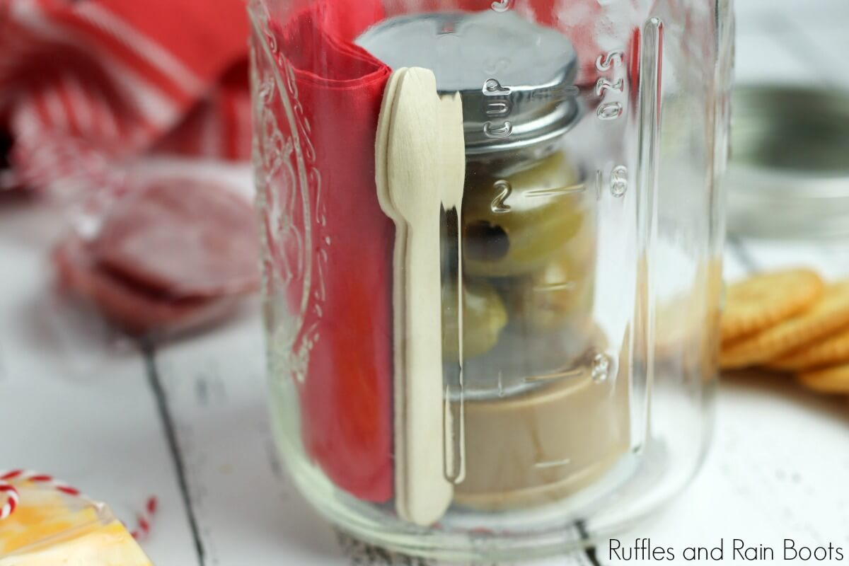 olives and peanut butter in a jar illustrating a step in the process of assembling the picnic date night in a jar