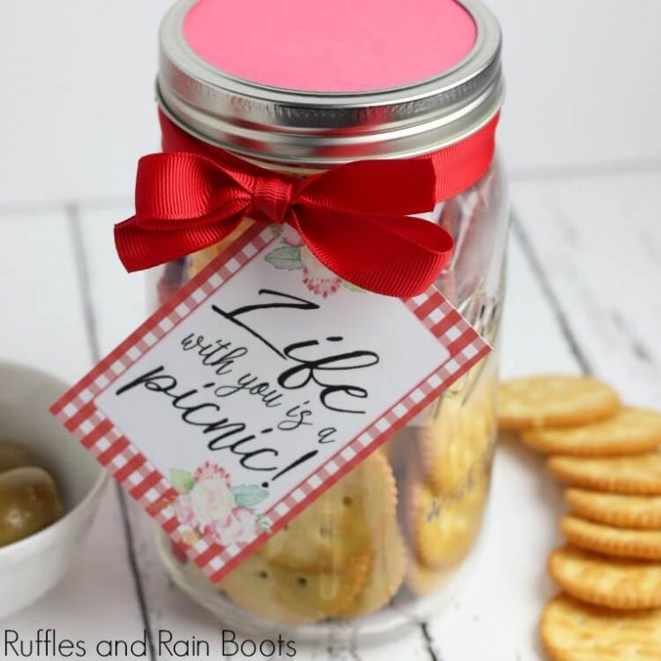 completed craft picnic date night in a jar craft with crackers and a bowl of olives on a white background with free printable tag which reads life with you is a picnic