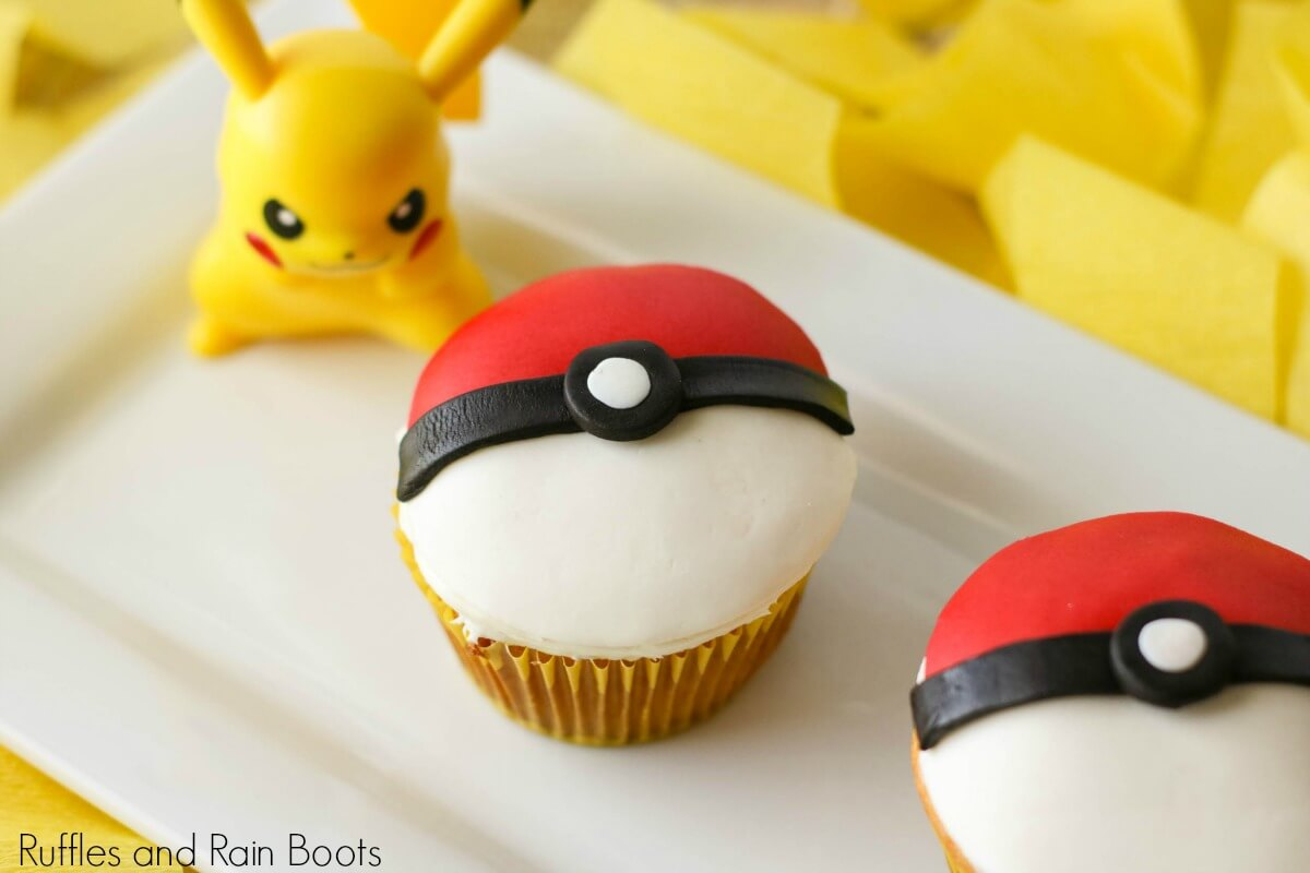 side view of a finished pokemon pokeball cupcake with pickachu on a plate