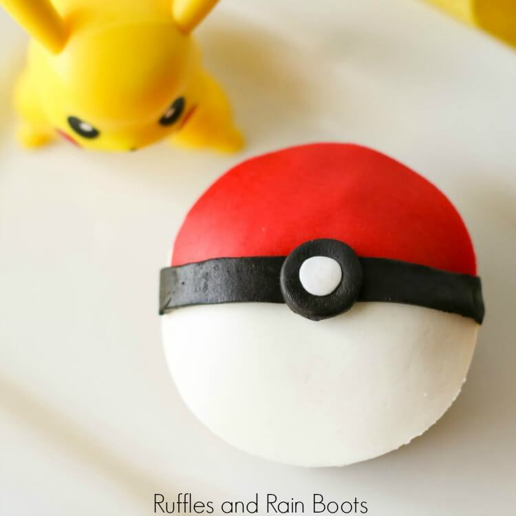 top-down view of a finished pokeball cupcake with pikachu figurine on a white background