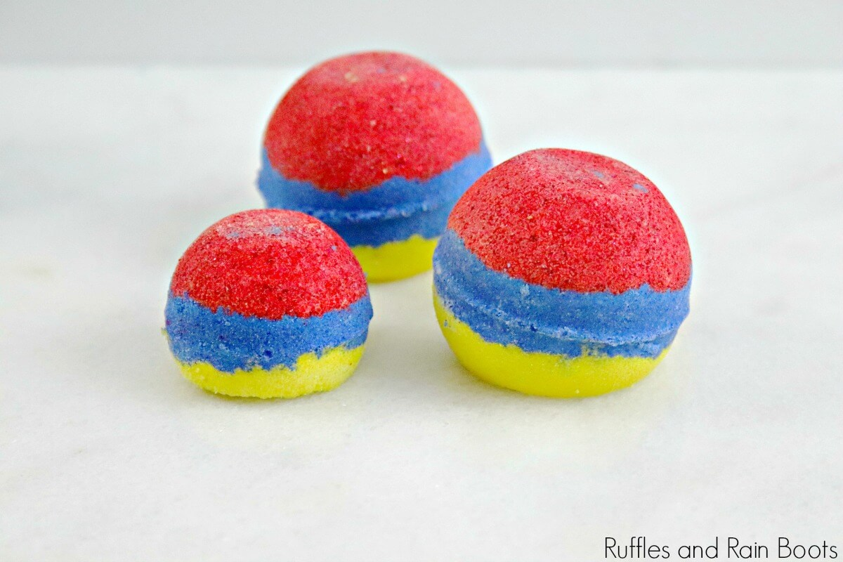 side view of red, blue and yellow Snow White bath bombs on a white background