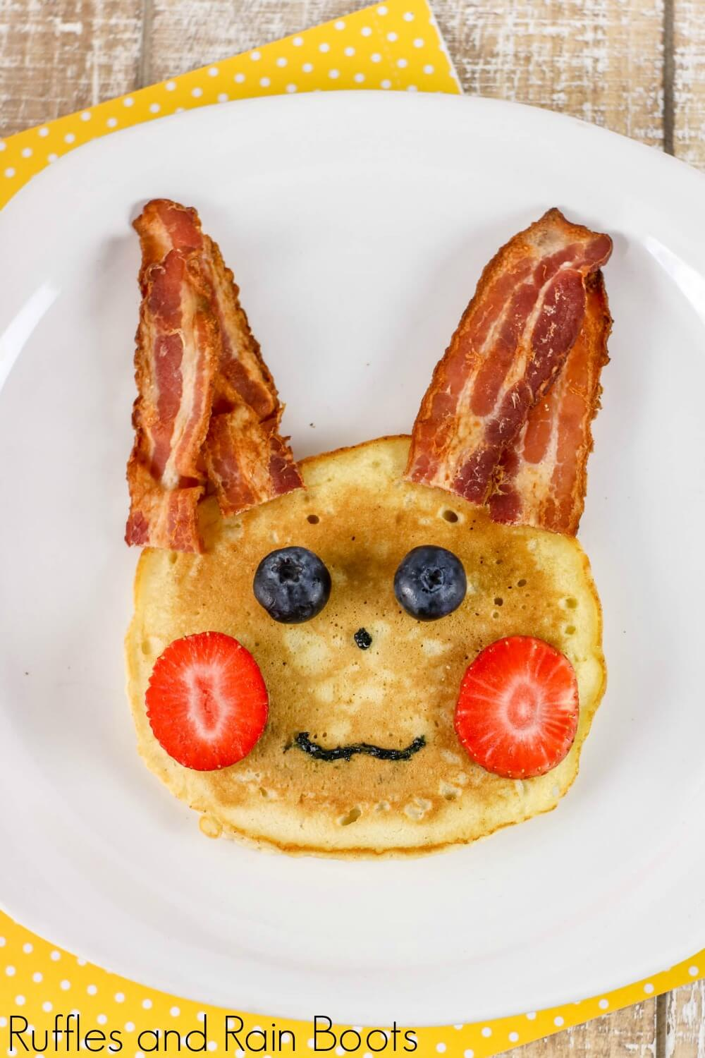 """pancake with bacon """"ears"""", strawberry """"cheeks"""", blueberry """"eyes"""", and icing for a nose and mouth made to depict a pikachu pokemon pancake on a plate"""