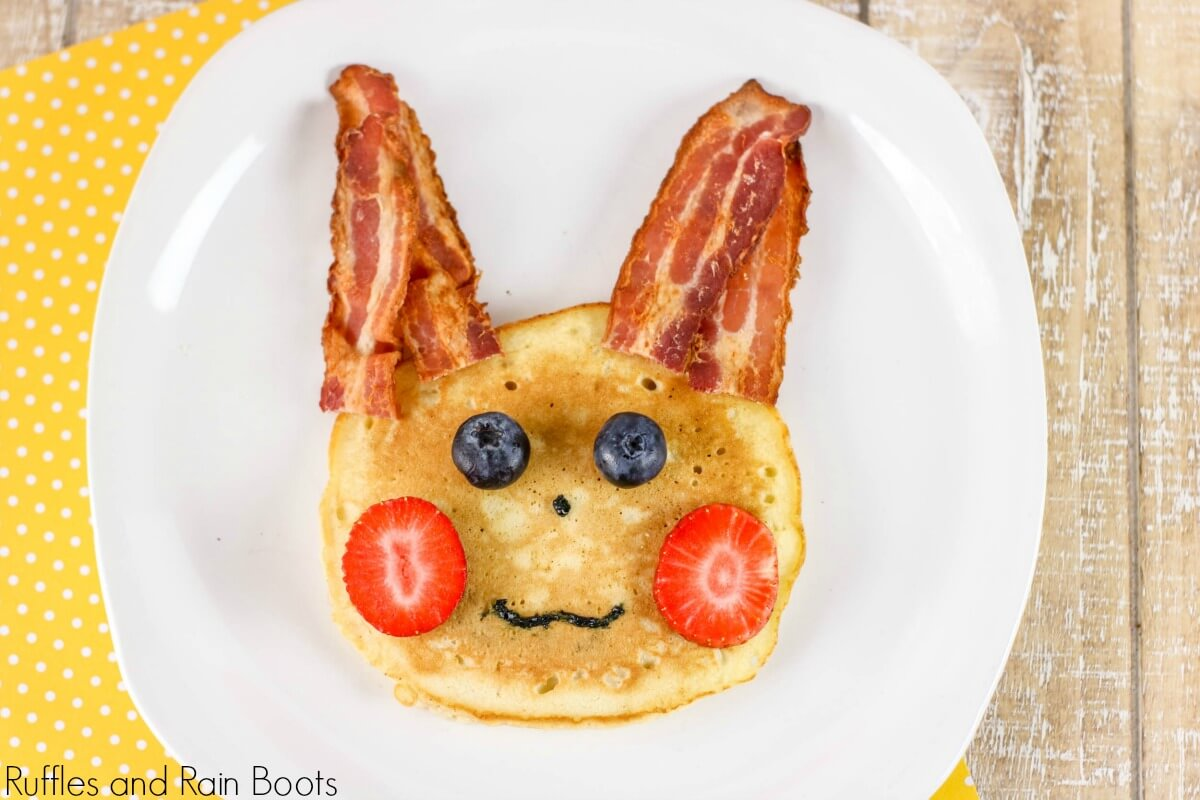 """pancake with bacon """"ears"""", strawberry """"cheeks"""", blueberry """"eyes"""", and icing for a nose and mouth made to depict pikachu pancake for a pokemon breakfast on a white plate"""