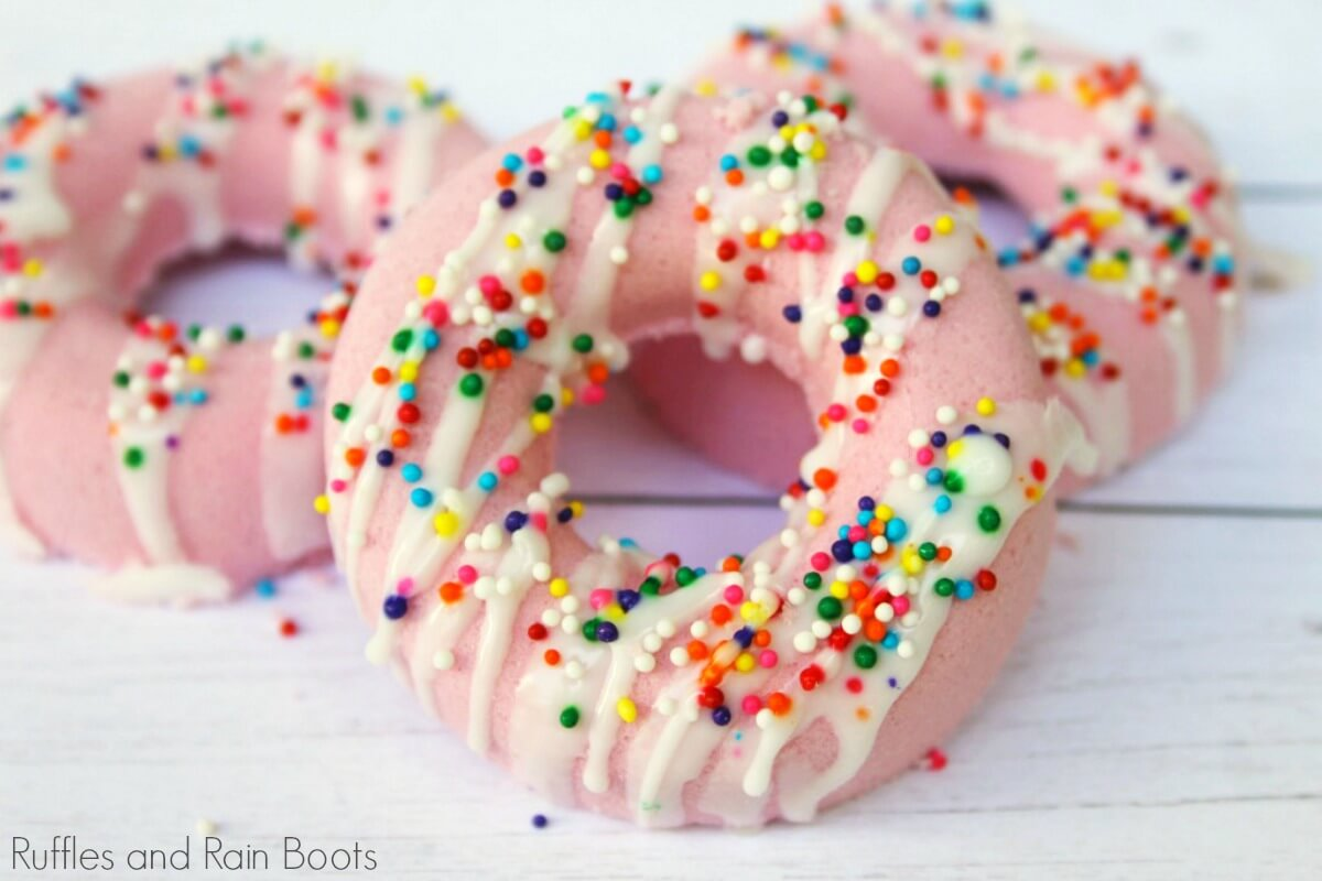 pink donut bath bombs covered in sprinkles on a white background
