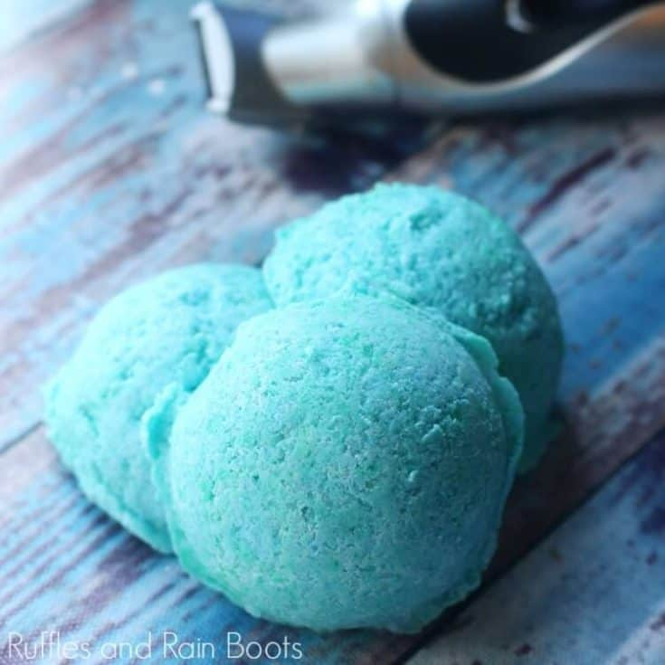 blue manly bath bombs on a blue and grey wood background with an electric razor in the background