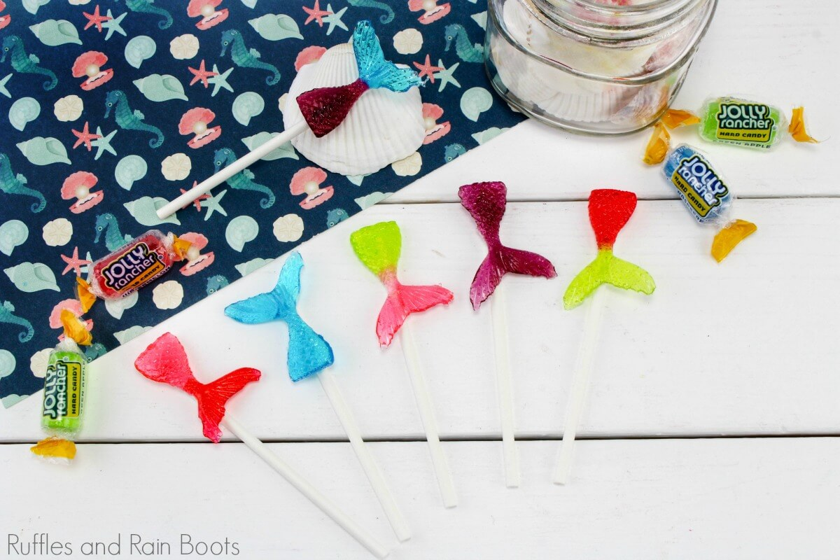 mermaid tail lollipops in multiple colors on a white background with some colorful paper and a shell with jolly rancher candies