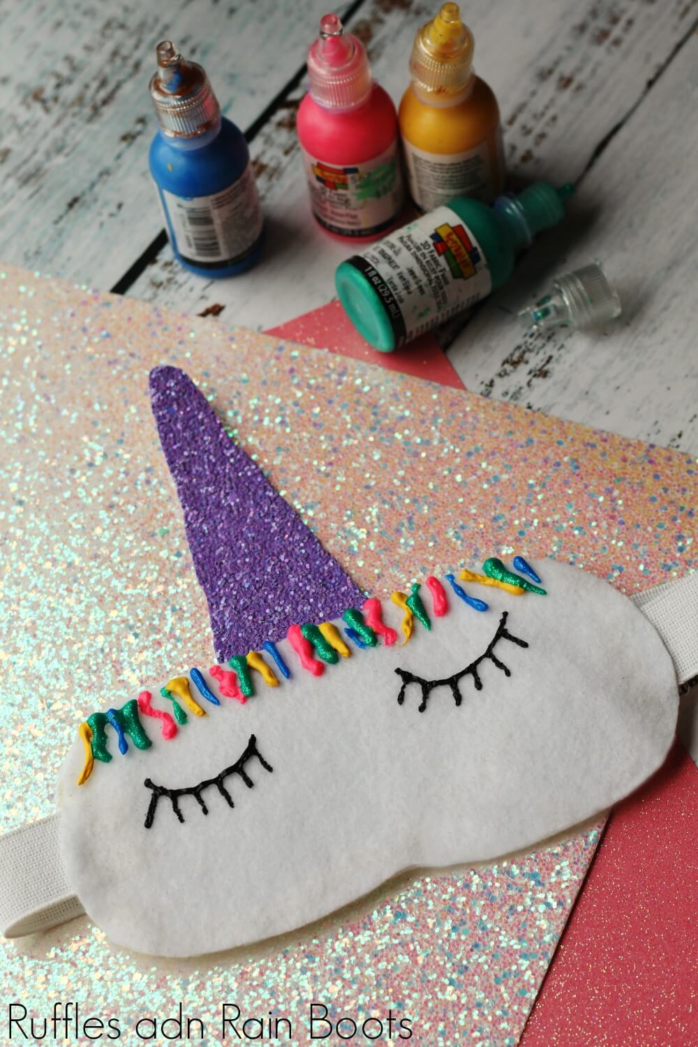 finished project of unicorn sleep mask on glitter paper with paint in background