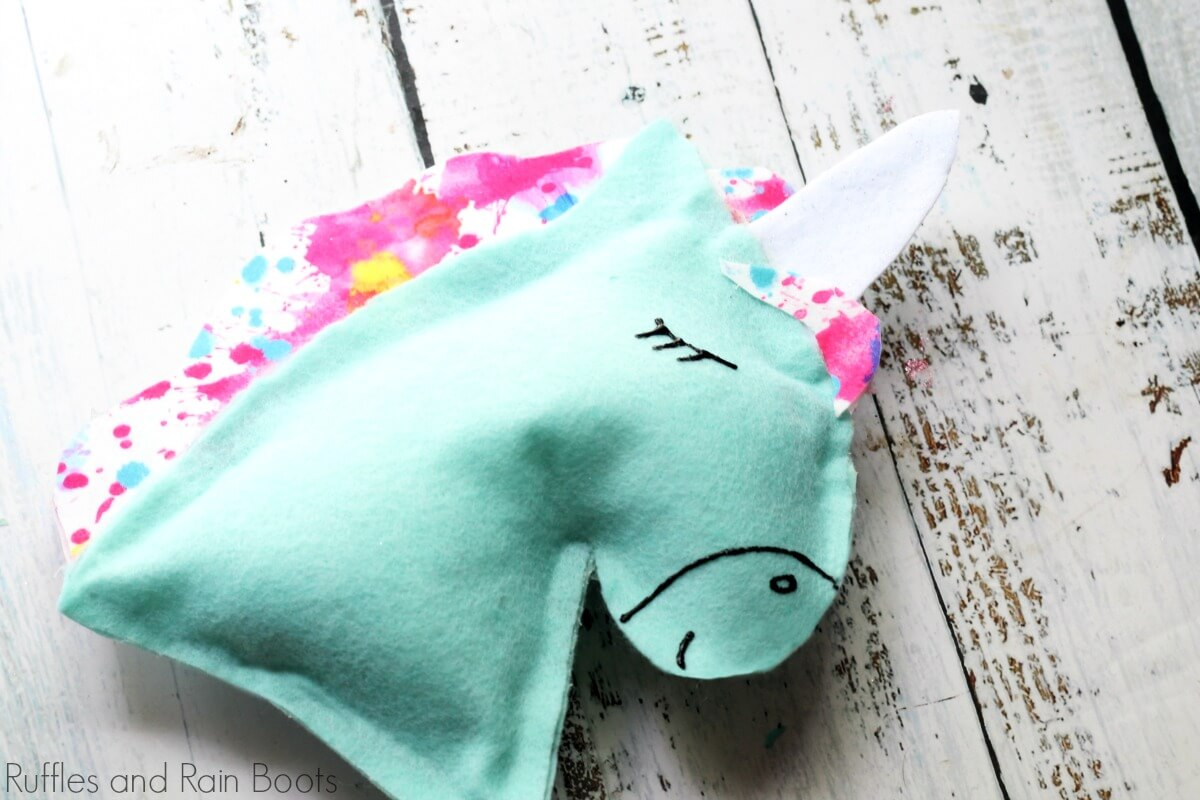 close up of unicorn pillow on wooden background