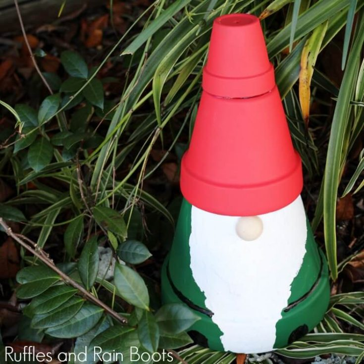 clay pot gnome statue in front of green foliage