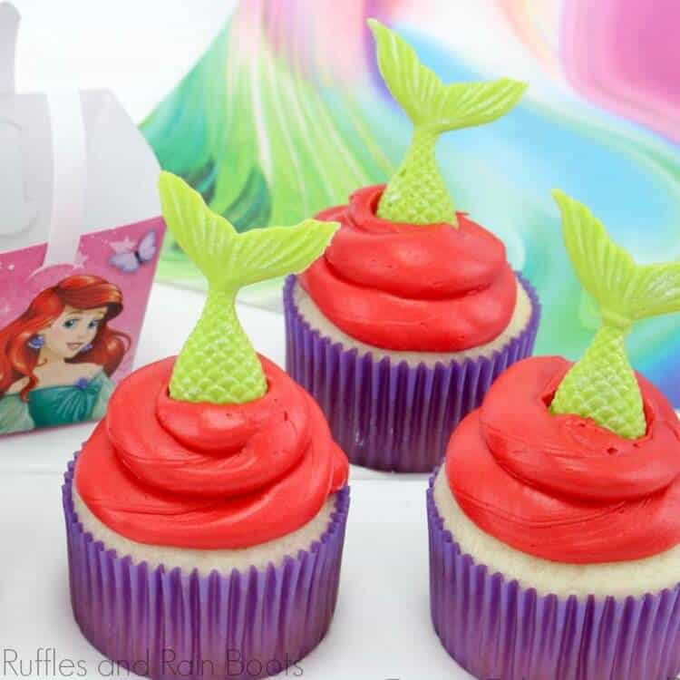 mermaid cupcakes with green tails, red icing and purple liners on a white background