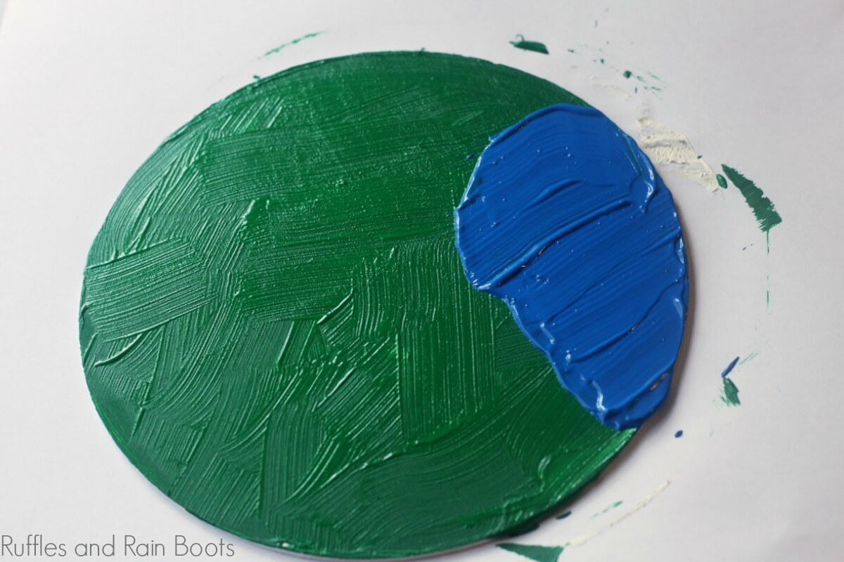 painting the base plate for your peg doll craft to have grass to stand on