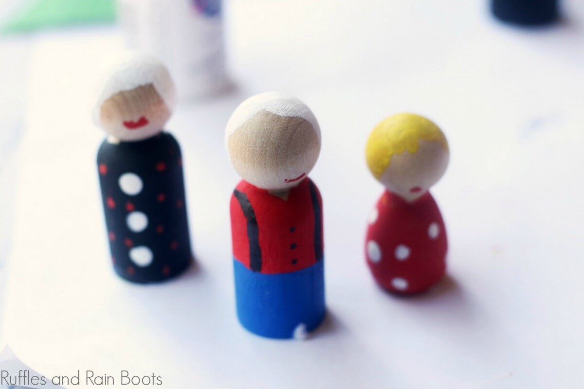 showing off the painted outfits of the gnome peg doll on white table