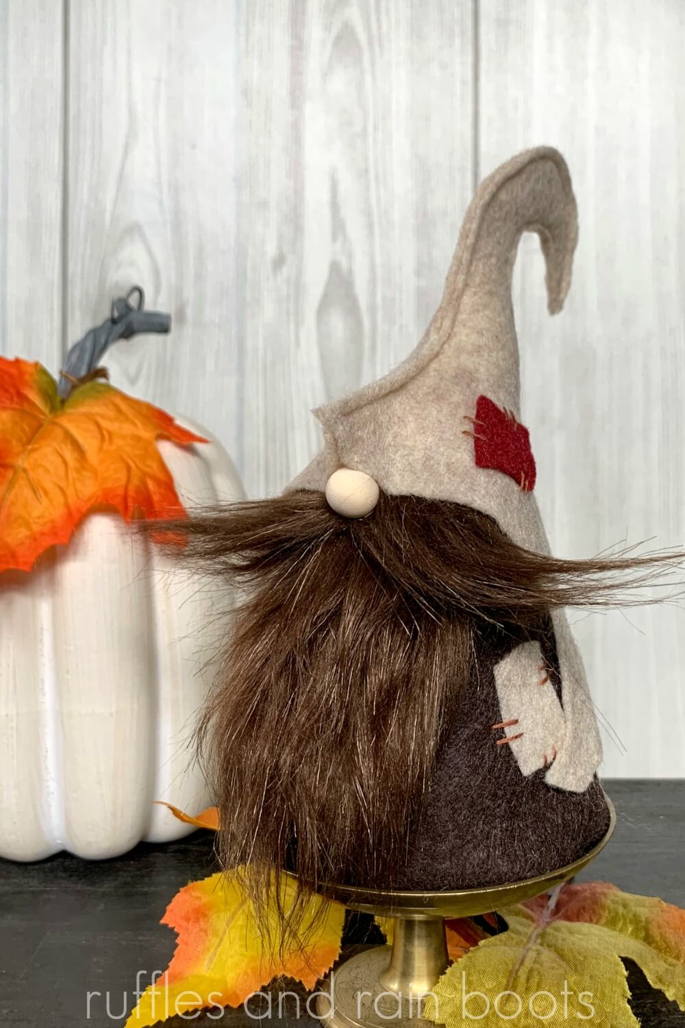fall gnome made from felt and faux fur styled in front of a pumpkin with fall leaves on a wooden table with shiplap wall