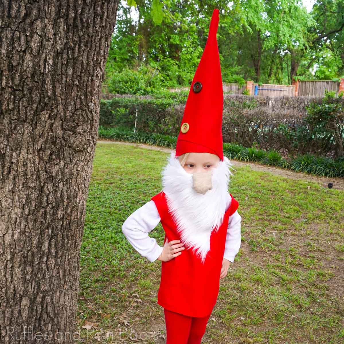 child dressed in a gnome hat and costume in a green yard how to make a gnome hat costume for kids